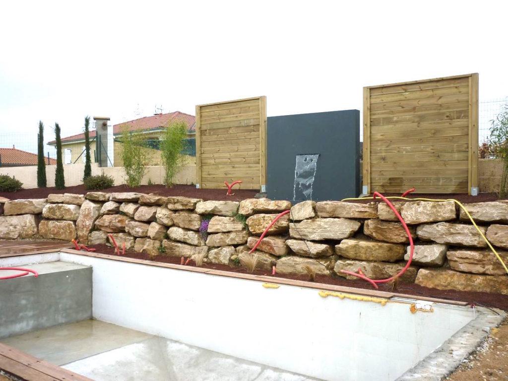 Installation d'un enrochement et panneaux décoratifs avec lame d'eau